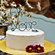 "Brides.com: Wedding-Worthy One-Tier Cakes. A Simple White Wedding Cake with a Wire ""Love"" Topper. Dress up a delicious, plain white wedding cake with a handcrafted rustic black wire that spells ""love,"" like this one from Funky Shack Art Studio.  See more white wedding cakes."