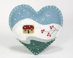 A handmade felt Christmas heart ornament, embroidered with a traditional Irish cottage in a snowy winter landscape, with birds in flight and bright red berries.