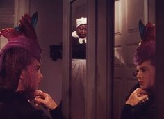 Hattie McDaniel as Mammy catches Vivien Leigh as the newly widowed Scarlett O'Hara Hamilton trying on a colorful hat in the civil war classic, 'Gone With The Wind'.