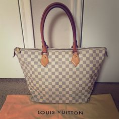Louis Vuitton Damier Azur Saleya MM Authentic Saleya MM tote in great condition. No cracks in the canvas or leather. A few marks on the bottom from normal use but no exposed piping.  One pen mark on canvas (see additional listing for more pics).  Handles have a nice patina and a couple of scuffs, and zipper runs well. Interior in good condition and has been cleaned professionally - no pen marks or noticeable stains (see pic). Has a slight perfume smell and a little leftover glitter inside…