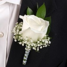 A boutonniere of roses and baby's breath wrapped in satin ribbon