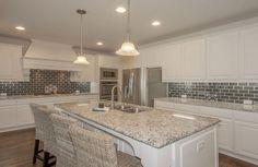 Crisp, updated kitchen // Light granite, green subway tile backsplash, white cabinetry, stainless