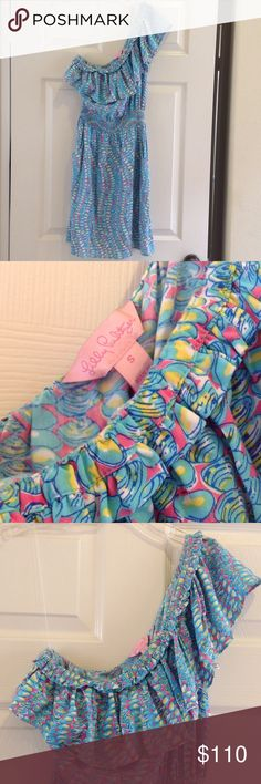 Lilly Pulitzer print, rayon dress. Size S. Lilly Puliter, print dress. Blue, turquoise, pink, yellow and white colored. 100 % rayon. Elastic waist with two pockets in front.  Sleeveless on one side; off shoulder on the other. Ruffle on top. Size S. Lilly Pulitzer Dresses