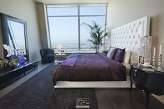 Casa Bedroom with White Bed and Purple Quilt near White Padded Headboard