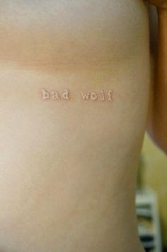 Bad wolf white ink lettering tattoo