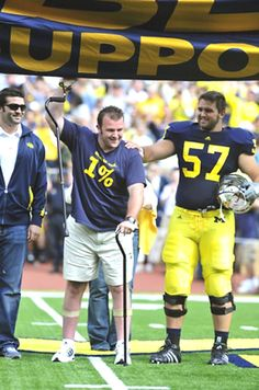 BROCK MEALER, center, walks onto the field before a 2010 University of Michigan football game with his brother, Elliott, right, by his side....