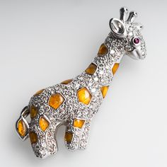 This lovely giraffe pendant is pavé set with round brilliant cut diamonds and accented with orange resin-enamel spots. The face and ears are molded and the eye is a ruby. The brooch is crafted of solid 18k white gold and is in very good overall condition.