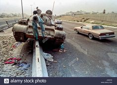 Cars drive past a destroyed Iraqi Army Type 69 tank left behind by retreating soldiers following the liberation of Kuwait March 1, 1991 in Kuwait City, Kuwait. After four days of fighting, all Iraqi troops were expelled from Kuwait, ending a nearly seven-month occupation of Kuwait by Iraq. Iraqi Army, Armored Fighting Vehicle, Iraq War, War Photography, Modern Warfare, Car Photos, Afghanistan, Troops, Historia