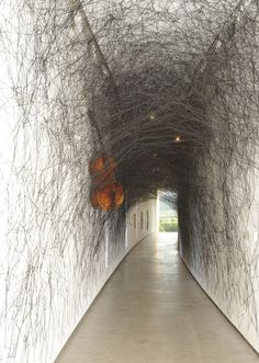 "Internationally acclaimed artist Chiharu Shiota has transformed the TWMA Vista Walk with an elaborate new installation. A double bass has been cocooned within an intricate and dense web of black yarn which then proliferates in countless layers throughout the space. As the artist describes, the labour intensive experience of creating these complex networks of thread is a means of giving physical presence to her own emotional states: ""The threads are interwoven into each other. Get entangled."