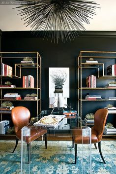 With the use of a lucite desk and minimalistic open shelving, the black walls in this space scream sophistication. Displayed on textured gold shelves, the colorful bindings on the books are strategically used as artwork to frame the contrasting white picture in the center. This energetic office is complete with a modern and dramatic light fixture, and a lighter blue oriental-style rug.