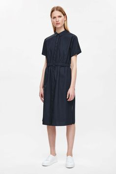 Designed to come in at the waist, this dress is made from soft cotton poplin with an elastic gathering. A shirt style, it has a narrow collar, large patch pockets and slits on both sides.