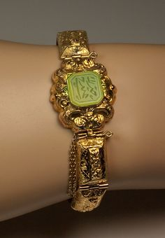 A Georgian Gold and Jade Bracelet, circa 1830. An ornate hollow 18K gold bracelet with embossed and hand engraved decorations is set with an octagon-cut jade engraved with an unidentified Eastern script (Arabic or Kufic?).