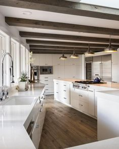 Clean lines and sleek, white surfaces create this striking modern kitchen. Reclaimed wood ceiling beams and floors add a raw, rustic touch to the polished space.