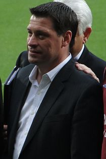 """Antony Richard """"Tony"""" Cottee (born 1965 in Newham, England)  of French Huguenot ancestry a English former professional footballer & manager who now works as a television football commentator.  As a player he was a striker from 1982 until 2001, notably playing in the top flight of English football for West Ham United, Everton and Leicester City. He was capped seven times by England, and played in the Football League for Birmingham City, Norwich City and Millwall. He also had a spell in…"""