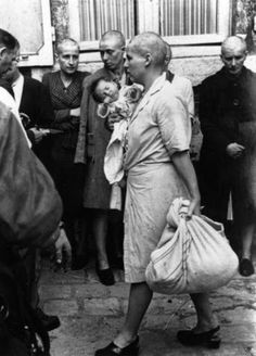 A French woman collaborator and her baby, whose father is German, returns to her home followed by a throng of taunting townspeople after having her head shaven following the capture of Chartres by the Allies, August 1944. It appears that she is passing some women who suffered a similar fate. Photo by Robert Capa.