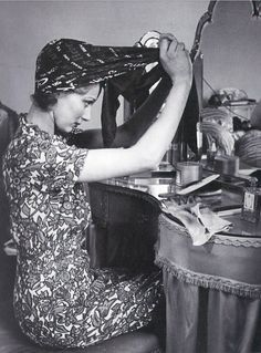 Actress Margaret Vyner fashions her scarf into a protective cover for her hair in preparation for her domestic chores, Picture Post 1941.
