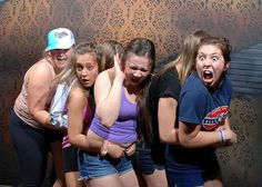 Camera catches people's reactions as a car comes crashing through the wall in a haunted house