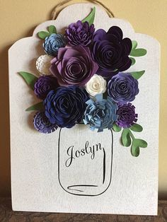 Beautiful wallhanging embellished with an old-fashioned canning jar that is personalized with either a first name (as in sample) or last name. Other embellishments include hand-rolled paper flowers made from premium card stock along with an accent of card stock leaves. Gorgeous! The