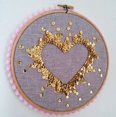 Handmade sequin art, each sequin has been sewn on individually to create a negative space heart. It is gold sequins on grey linen fabric, pale: