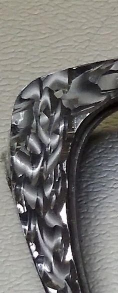 Particolare della lavorazione a mano con diamante, su plastica, nella parte superiore destra di un occhiale.