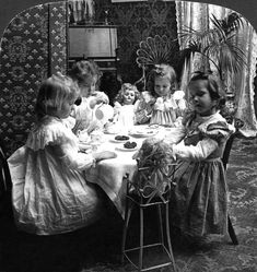 TEA PARTY, c1902. Four girls and their dolls sitting around a table and having a tea party. Stereograph, c1902
