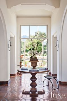 The front door opens onto a large entry foyer; glass doors and transom windows at the end of the space offer an immediate glimpse of the Santa Barbara mountains in the distance. The Portuguese pedestal table was found at Dos Gallos. Architecture Details, Interior Architecture, Interior Design, Interior Paint, Design Interiors, Poker, Transom Windows, Mediterranean Homes, Mediterranean Breakfast