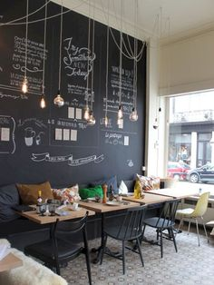 Modern and cheerful coffee shop decor with a chalkboard wa .- Modernen und fröhlichen Coffee-Shop Dekor mit einer Tafel Wand und hängenden G… Modern and cheerful coffee shop decor with a blackboard wall and hanging light bulbs - Coffee Shop Interior Design, Coffee Shop Design, Restaurant Interior Design, Coffee Shop Interiors, Coffee Cafe Interior, Design Shop, Small Restaurant Design, Cute Coffee Shop, Cozy Coffee