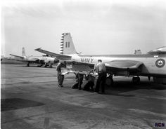 Crew of VF 870 Squadron load a Sidewinder Guided Missile on a Banshee aircraft for International Air Show in Toronto