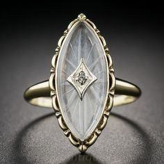 Just shy of 1 inch long, here is a charming navette (or marquise) shape dinner ring, circa 1930s. The ring shimmers with a carved rock quartz crystal, pierced in the center with a tiny twinkling single-cut diamond, set inside and atop a scalloped gold frame. Currently ring size 7. $75