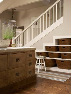 Reclaim wasted space under a staircase for storage. Wide-trim molding turns these staggered shelves into a strong architectural feature. Baskets add eye pleasing texture as they keep linens and other kitchen odds and ends corralled.