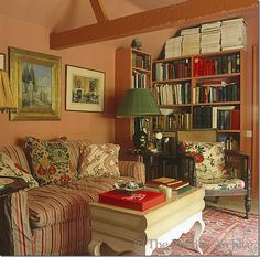 Room of the Day: another view of Nicky Haslam's cosy library with chintz, stripes in fabrics, fun coffee table, salmon walls, books and art - John Fowler's old hunting lodge 5.14.2013