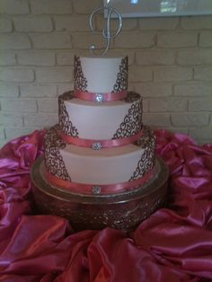 buttercream wedding cake pink buttercream with brown scrollwork and pink ribbons