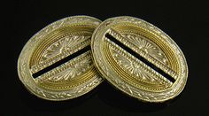 "An exuberant pair of Art Deco cufflinks with radiant sunburst centers.  The white gold centers are bisected by dramatic black enamel lines and surrounded by oval ""courses"" of engraved yellow gold.  The white gold borders complement the design with bold Art Deco motifs.  Crafted in 14kt white and yellow gold, circa 1925."