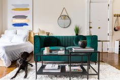 The emerald velvet sofa is from Wayfair, and the nesting coffee tables are from Ikea. Weaver is an original.