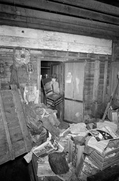 Crime lab specialist Jim Halligan carrys a chair through a doorway as he searches for evidence in the disorganized home of serial killer Ed Gein, Plainfield, Wisconsin on Nov. 20, 1957.