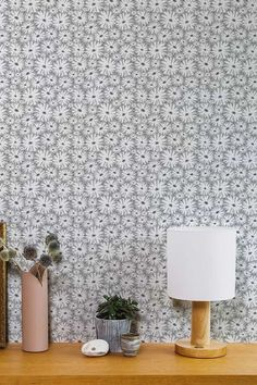 Inspired by textiles from the 1960's and 70's this cheerful, surface printed wallpaper has an all-over design of varying sized daisy heads #greyfloralwallpaper