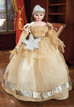 England,circa 1865. Value Points: with rarer lever eyes and original slit wig,the doll is wearing her original Christmas Fairy costume of loosely-woven gauze muslin with ivy berry silk bows,and with silver paper accessories including skirt trim,crown with pearl beading,and silver star wand.