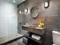 """To add flair in the compact space, we custom manufactured the outsized concrete trough sink in conjunction with Dare To Be Different. Gray slab tile and black grouted subway tile conspire a fresh """"wash and go"""" environment. RELATED: 64 Bathroom Decorating Ideas"""