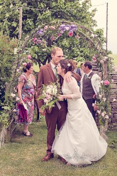 country wedding photographs kiss under floral archway. Photography by one thousand words wedding photographers