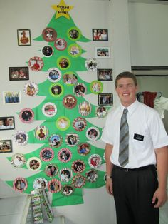 "Paper Christmas tree with picture ornaments my missionary decorated himself.  Added a ""Called to Serve"" star to top it off!  I just folded the tree and sent blue painters tape for the wall. Easy to mail, and takes up no space at all in their tiny apartments!"