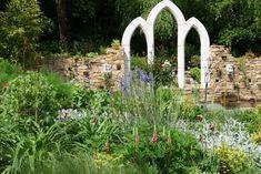 Spitzbögen und Mauern aus Naturstein bilden einen ungewöhnlichen Rahmen für den angrenzenden Gartenteich. Die üppige Staudenpflanzung unterstreicht die wildromantische Ruinen-Szenerie