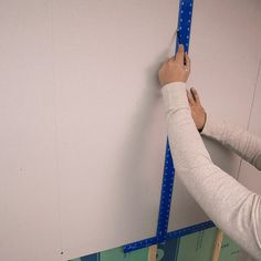 marking the studs on the outside of the drywall panel with a square