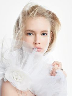 """Snow Day – Dior taps Emma Landen for its spring 2013 campaign of brightening products named DiorSnow. The blonde beauty looks angelic in all white looks as well as the limited edition """"Icy Halos"""" collection which features eye, face and lip products and nail varnishes in cool blue, pink and white hues inspired by the beauty of Iceland."""