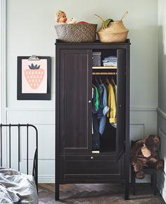 Deux paniers sur le dessus d'une armoire remplie de vêtements d'enfant.