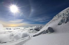 Three climbers making their way down after reaching the summit of Huayna Potosi mountain in Bolivia. They stopped to admire the breathtaking view as the sun had come up behind them.
