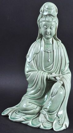 A 19TH CENTURY CHINESE CELADON GLAZED FIGURE OF GUANYIN modelled seated holding a scroll. 11.75ins high.