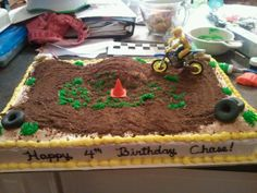 "Dirt bike track - This was a birthday cake for a young man who loves dirtbikes. The dirtbike was a toy, chocolate animal cracker ""dirt"", buttercream orange cone, shredded wheat hay bales, and fondant tires."