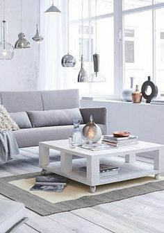 Sofa area in grey, white, and wood with hanging lamps and a coffee table made of a pallet