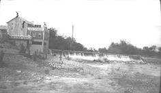 """Probably Walter Hill Dam near Murfreesboro, Tennessee. Shows power plant to the left of dam with """"Murfreesboro Light & Power Co."""" painted on it. Part of Tennessee Highway Dept. photographs in Middle Tennessee & Chattanooga."""