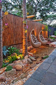 décoration jardin extérieur avec sol en pierre grise, fauteuils suspendus et arbres exotiques